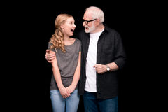 Grandfather and teenage granddaughter. Grandfather hugging excited granddaughter isolated on black Stock Photos
