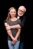 Grandfather and teenage granddaughter. Smiling grandfather hugging teenage granddaughter isolated on black Stock Photo