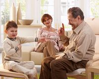 Grandfather telling telling a story to grandson. Happy smiling grandfather telling a story to his grandchild, grandmother listening in background Royalty Free Stock Image