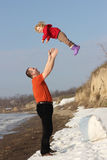 Grandfather throwing his granddauther in the air Royalty Free Stock Photography
