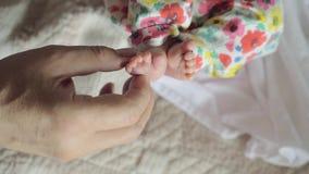 Grandfather touching feet of newborn baby