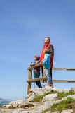 Grandfather and two grandchildren in mountains. Grandfather and two grandchildren admire the scenery on the cliff stock images