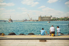 Grandfather and two grandsons looking into distance at Haydarpasa Train Station on Bosphorus Royalty Free Stock Photos