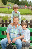 The grandfather of two grandsons sit on bench Stock Photo