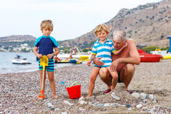 Grandfather and two little kid boys on ocean beach Stock Photos