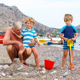 Grandfather and two little kid boys on ocean beach Royalty Free Stock Photography