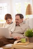 Grandfather using computer at home Royalty Free Stock Images