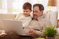 Grandfather using computer at home Royalty Free Stock Image