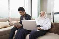 Grandfather using laptop while grandson reading book on sofa at home Stock Image