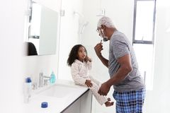 Grandfather Wearing Pajamas In Bathroom Shaving Whilst Granddaughter Watches stock image