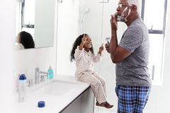 Grandfather Wearing Pajamas In Bathroom Shaving Whilst Granddaughter Watches royalty free stock image