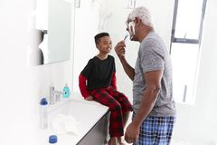 Grandfather Wearing Pajamas In Bathroom Shaving Whilst Grandson Watches royalty free stock images