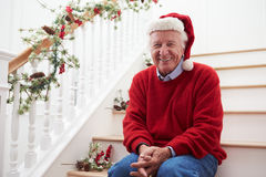 Grandfather Wearing Santa Hat Sitting On Stairs At Christmas Stock Images