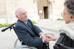 Grandfather in wheelchair and wife outside church Royalty Free Stock Photo