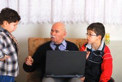 Grandgather and grandsons. Grandchildren learn grandfather to work on laptop royalty free stock photos