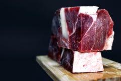 Grandi bei pezzi della carne striata del manzo per l'alimentazione cruda dei gatti e dei cani sul bordo di legno davanti a fondo  fotografia stock