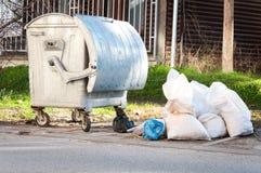 Grandi bidoni della spazzatura del bidone della spazzatura del metallo in pieno della lettiera di straripamento che inquina la vi Fotografie Stock Libere da Diritti