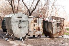 Grandi bidoni della spazzatura del bidone della spazzatura del metallo in pieno della lettiera di straripamento che inquina la vi Fotografie Stock