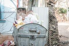 Grandi bidoni della spazzatura del bidone della spazzatura del metallo in pieno della lettiera di straripamento che inquina la vi Immagine Stock
