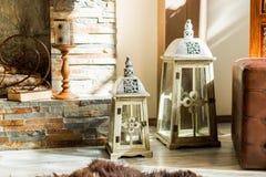 Grandi candele accanto al camino elegante Lanterna bianca per la candela Lanterna chiusa per la candela al pavimento di legno Sti fotografia stock libera da diritti