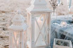 Grandi candele accanto alla messa a punto elegante della tavola in pastelli blu per le nozze di spiaggia fotografia stock libera da diritti