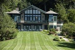 Grandi casa della proprietà del palazzo e prato inglese di lusso dell'erba Fotografia Stock Libera da Diritti
