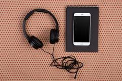 grandi cuffie nere, smartphone bianco e blocco note nero su craf fotografie stock libere da diritti