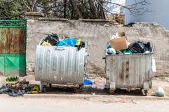 Grandi due bidoni della spazzatura del bidone della spazzatura del metallo in pieno della lettiera di straripamento che inquina l Immagini Stock Libere da Diritti
