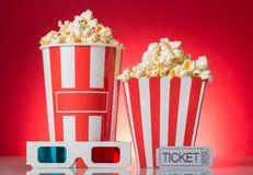 Grandi e piccoli contenitori di popcorn, un biglietto al cinema, vetri 3d su rosso Immagini Stock