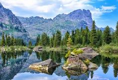 Grandi frammenti di roccia in acqua del lago della montagna Fotografia Stock