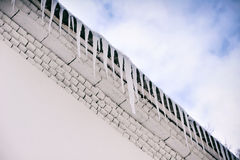 Grandi ghiaccioli che pendono dal tetto Fotografie Stock Libere da Diritti