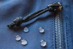 Grandi gocce di acqua sui vestiti impermeabili fermo della tasca delle chiusure lampo fotografie stock