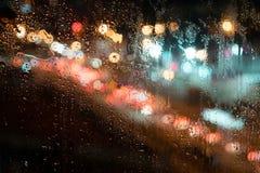 Grandi gocce di pioggia sul vetro, contro lo sfondo della via di notte Immagine Stock Libera da Diritti