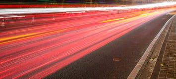 Grandi luci dell'automobile della strada di città alla notte Fotografia Stock