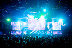 Grandi mani della folla di concerto in aria con gli effetti della luce fotografia stock libera da diritti