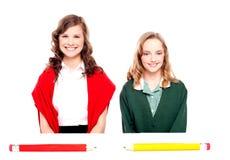 Grandi matite che si trovano davanti a due ragazze del banco Fotografie Stock