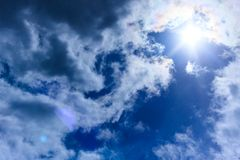 Grandi nuvole lanuginose alte nel cielo Il sole splende attraverso le nuvole Immagini Stock