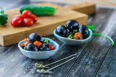 Grandi olive nere, ciliegia e prezzemolo sotto la marinata in una vista laterale della ciotola ceramica fotografia stock libera da diritti