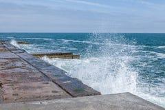 Grandi onde sulla costa rocciosa e sul mare blu fotografie stock