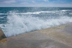 Grandi onde sulla costa rocciosa e sul mare blu fotografia stock