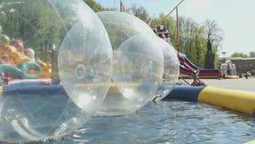 Grandi palle gonfiabili che galleggiano sull'acqua in stagno video d archivio