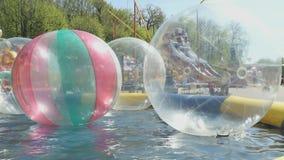 Grandi palle trasparenti gonfiabili dell'acqua all'aperto stock footage
