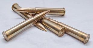 Grandi pallottole del fucile di calibro su un fondo bianco Fotografie Stock Libere da Diritti