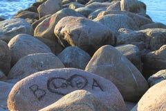 Grandi pietre dalla spiaggia al tramonto e al lovers& x27; iscrizione su una pietra Fotografia Stock Libera da Diritti