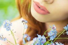Grandi ragazze sexy delle labbra con i fiori blu in sue mani Fotografia Stock
