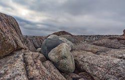 Grandi rocce sulla riva del mare di Barents contro lo sfondo di un cielo tempestoso scuro Immagini Stock Libere da Diritti