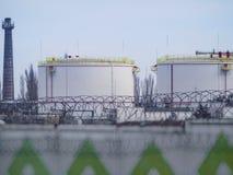Grandi serbatoi dell'olio in un'area recintata Fotografia Stock
