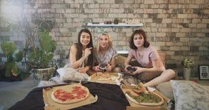 Grandi signore sorridenti in pigiami sul letto che gioca in un PlayStation che mangiano pizza e che godono insieme del tempo stock footage