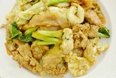 Grandi tagliatelle di riso fritte con carne di maiale e la verdura in salsa di soia nera sul piatto Immagine Stock