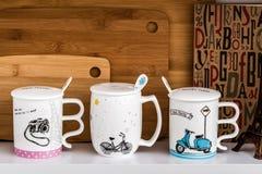Grandi tazze bianche con i cucchiai e bicicletta, motociclo e macchina fotografica De Fotografie Stock Libere da Diritti
